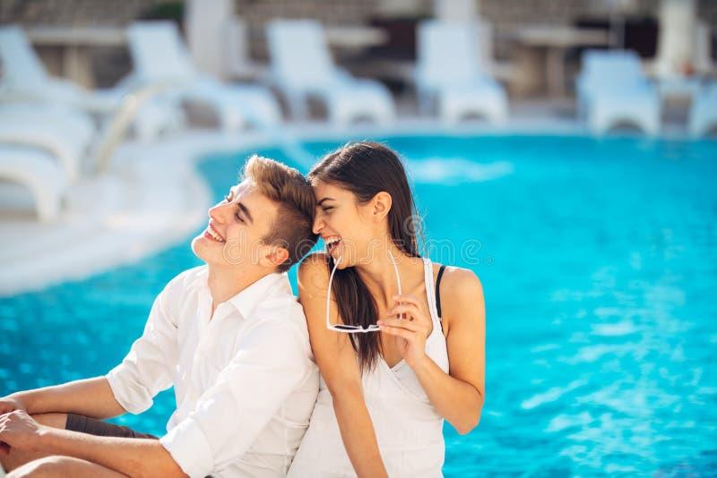 Vacances affectueuses de dépense de couples sur la piscine tropicale de station de vacances Lune de miel de nouveaux mariés sur l image libre de droits
