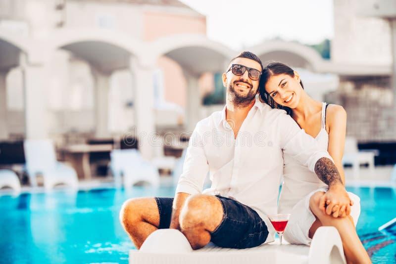 Vacances affectueuses de dépense de couples sur la piscine tropicale de station de vacances Lune de miel de nouveaux mariés sur l image stock