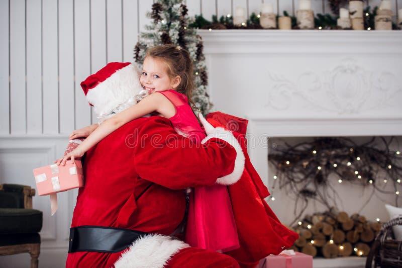 Vacances, célébration, enfance et concept de personnes - petite fille de sourire étreignant avec le père noël au-dessus de l'arbr photo stock