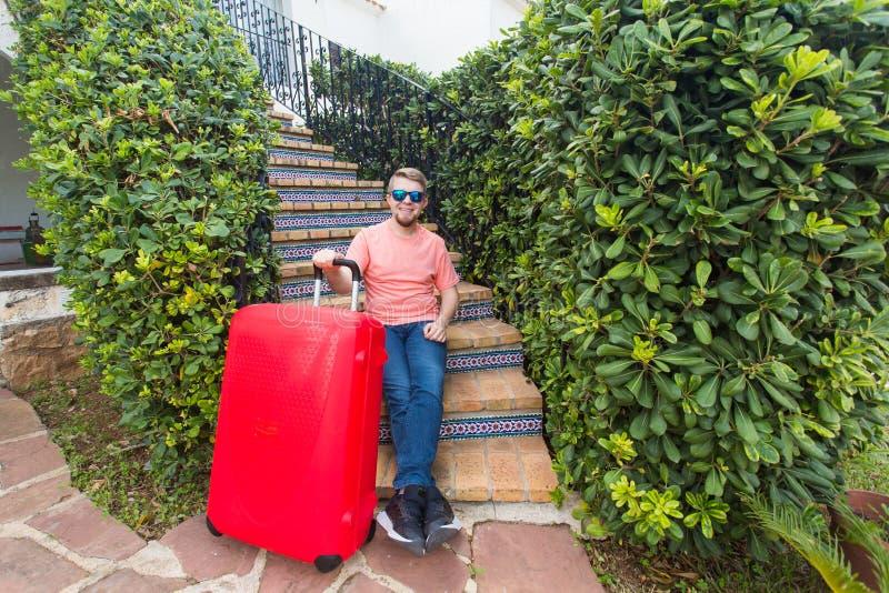 Vacances, déplacement et concept de personnes - homme avec la valise rouge de voyage reposant sur des escaliers sa maison images stock