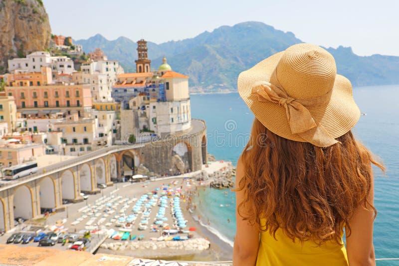 Vacances d'été en Italie Vue arrière de jeune femme avec le chapeau de paille et la robe jaune avec le village d'Atrani sur le fo photo stock