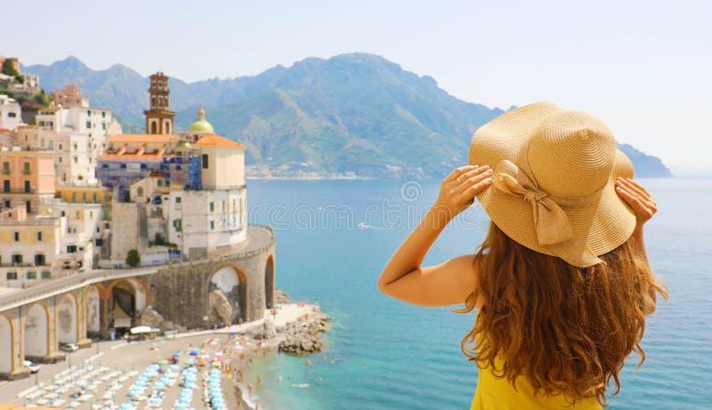 Vacances d'été en Italie Vue arrière de jeune femme tenant son chapeau avec le village d'Atrani sur le fond, côte d'Amalfi, Itali image libre de droits