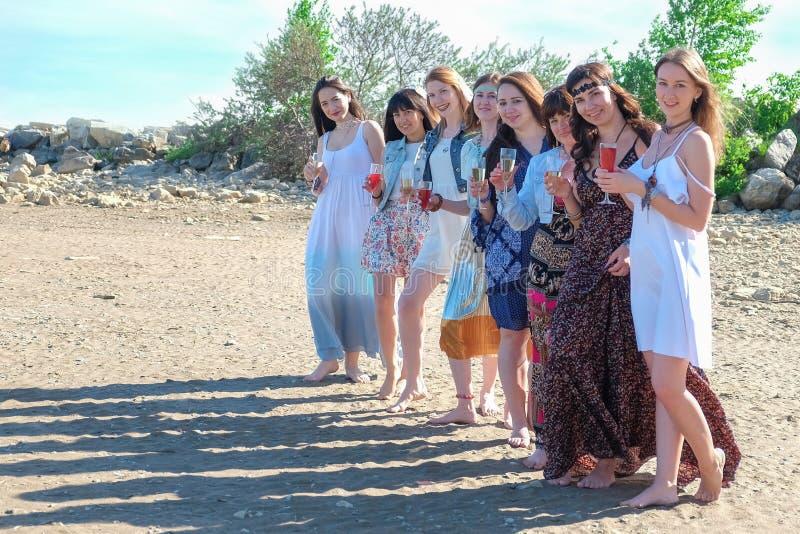Vacances d'été et concept de vacances - filles hippies de sourire avec des boissons sur la plage photographie stock