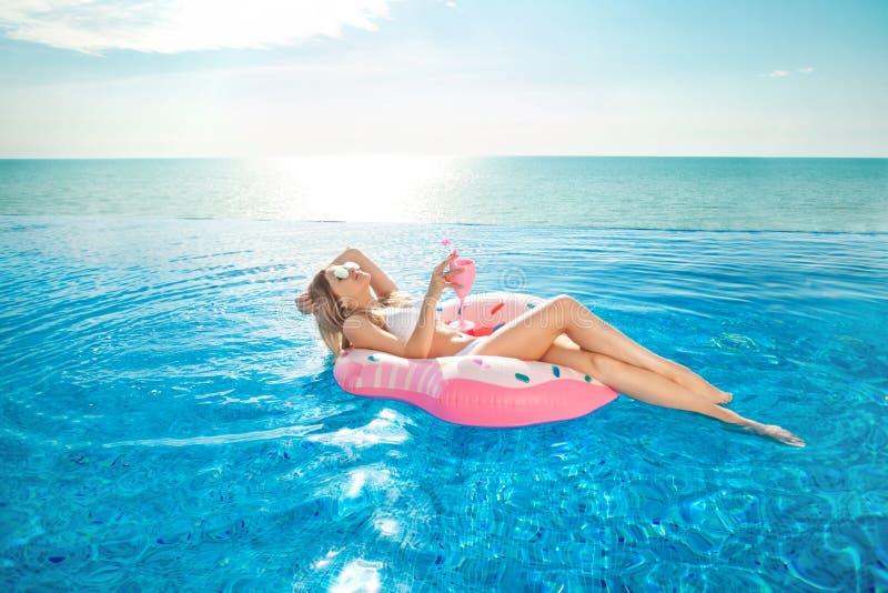 Vacances d'été Femme dans le bikini sur le matelas gonflable de beignet dans la piscine de STATION THERMALE photos libres de droits