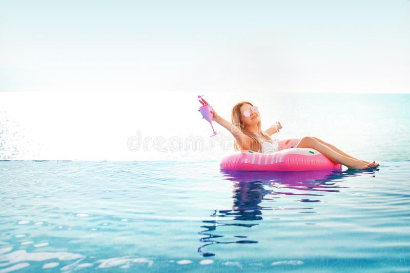 Vacances d'été Femme dans le bikini sur le matelas gonflable de beignet dans la piscine de STATION THERMALE image stock