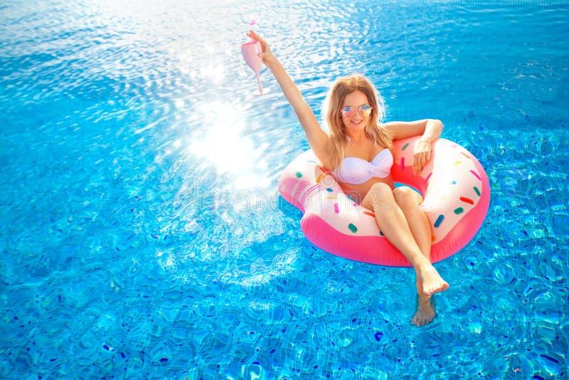 Vacances d'été Femme dans le bikini sur le matelas gonflable de beignet dans la piscine de STATION THERMALE image libre de droits