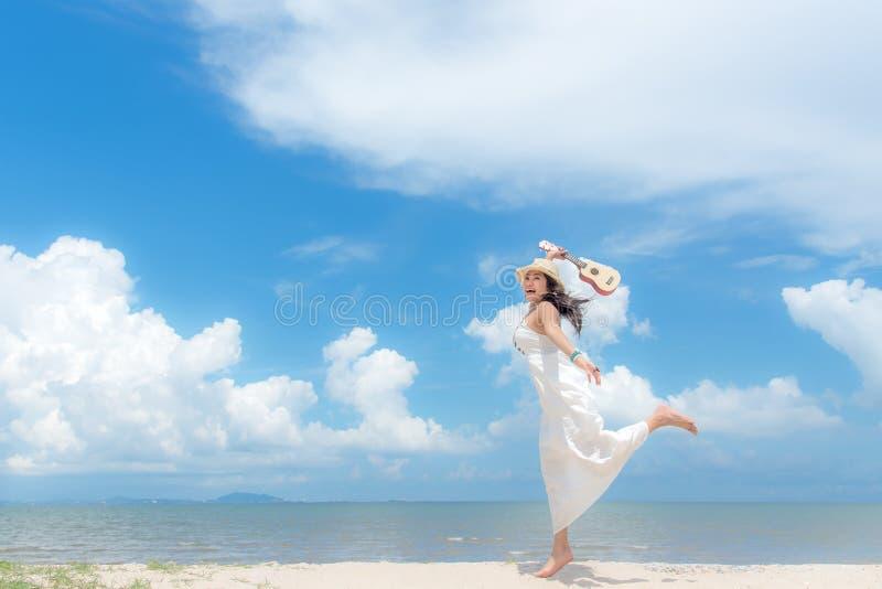 Vacances d'été Femmes asiatiques sentantes détendant et jouant une ukulélé sur la plage, photos stock