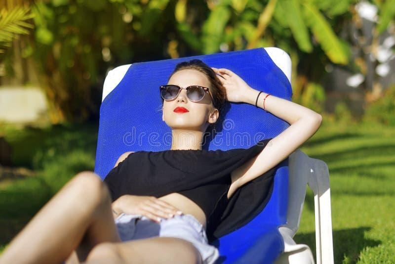 Vacances d'été La fille de mode en verres de soleil détend À l'arrière-plan un palmier Concept de vacances photo stock