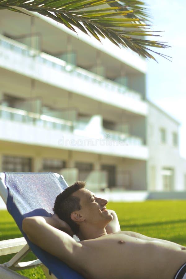 Vacances d'été Prendre un bain de soleil de jeune homme À l'arrière-plan un palmier Concept de vacances L'indépendant d'homme se  image libre de droits