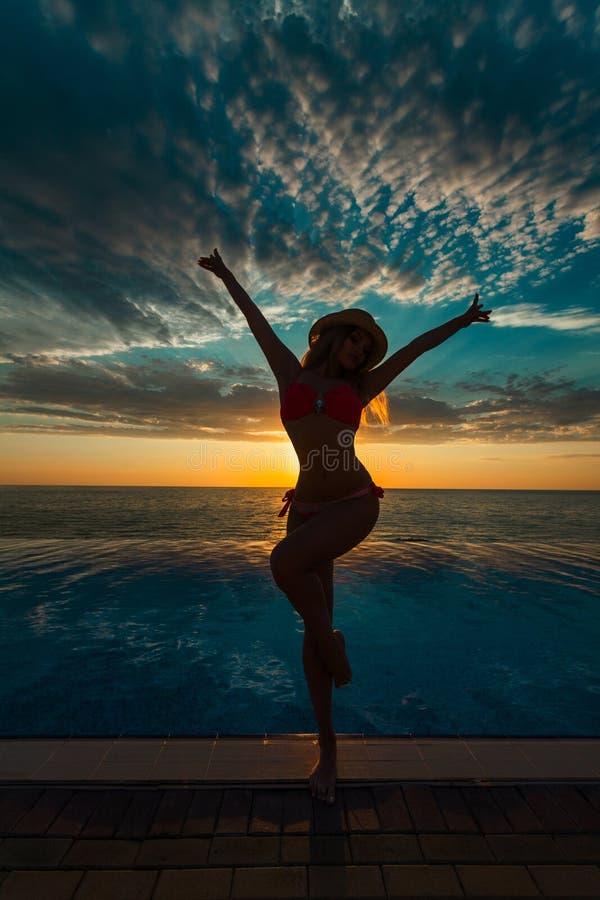 Vacances d'été Silhouette de femme de danse de beauté sur le coucher du soleil près de la piscine avec la vue d'océan photographie stock