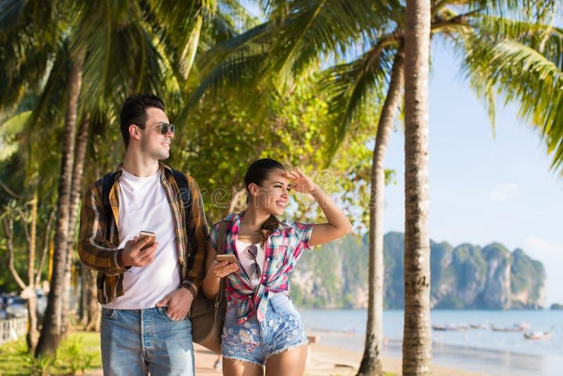Vacances d'été tropicales de marche de palmiers de plage de couples, les beaux jeunes regardant la mer, vacances de femme d'homme photos libres de droits