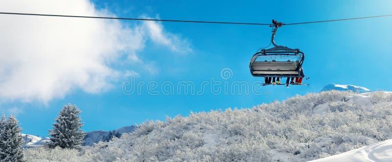 vacances d'hiver - ascenseur de chaise au-dessus de paysage neigeux de montagne photo libre de droits