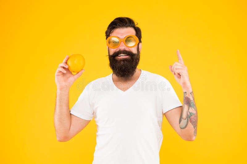 Vacances d'?t? Hippie barbu d'homme dans des lunettes de soleil oranges sur le fond jaune Source de rafraîchissement Nutrition d' image libre de droits