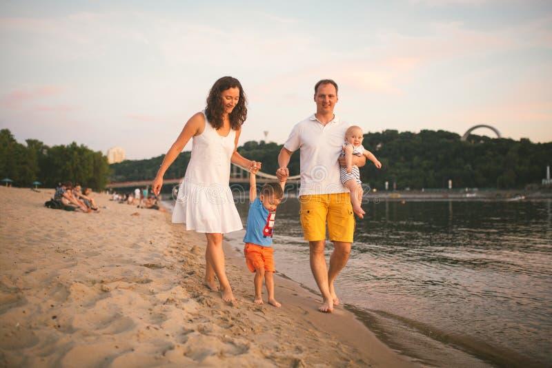 Vacances de famille en ?t? Jeune pied caucasien de famille marchant la plage sablonneuse aux pieds nus, eau de rivi?re de rivage  photos stock