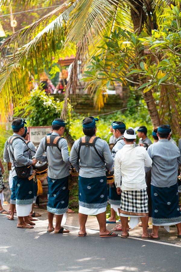 Vacances de Galungan Un groupe des hommes préparant la représentation sur des tambours La vue du dos ville courante de coucher du image stock