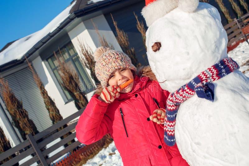 Vacances de l'hiver Extérieur de position de fille près de la maison faisant le bonhomme de neige mangeant le plan rapproché espi photographie stock libre de droits