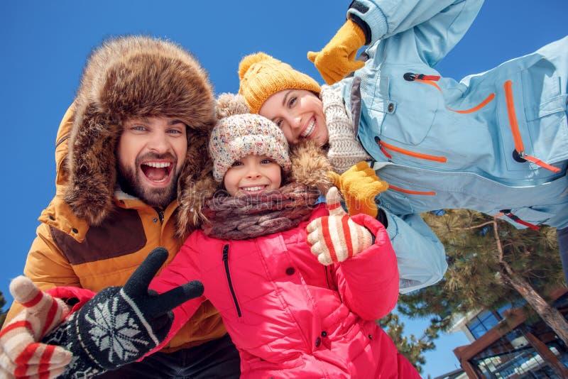 Vacances de l'hiver Le temps de famille montrant ensemble dehors le pouce se lève à la vue inférieure heureuse de caméra images stock