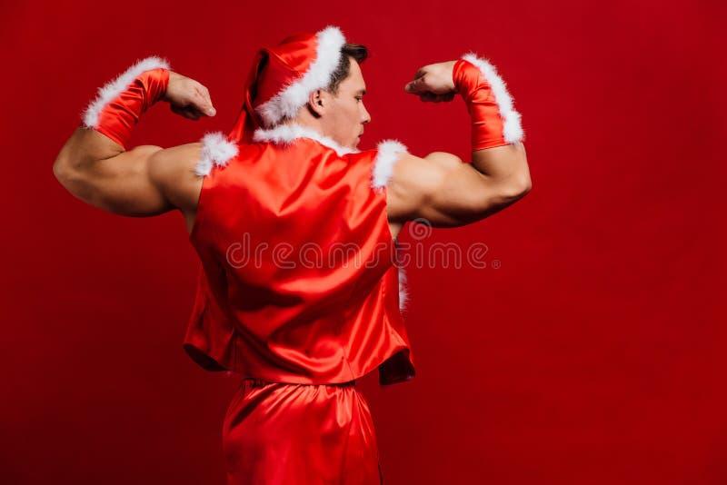 Vacances de Noël chapeau de port fort sexy du père noël Jeune homme musculaire Fond rouge images libres de droits