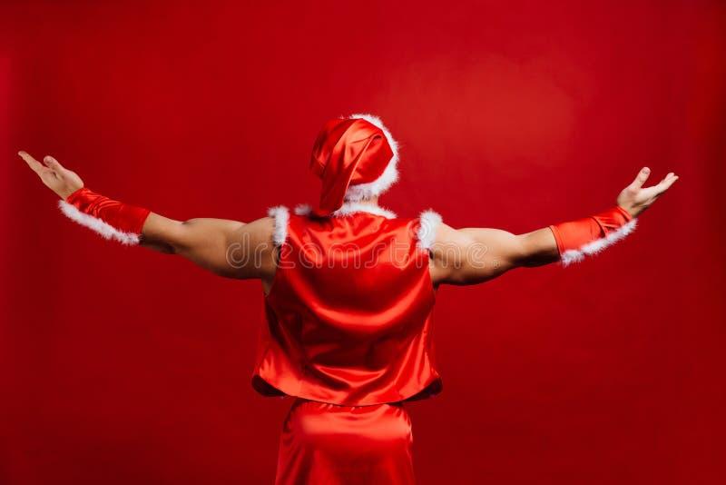 Vacances de Noël chapeau de port fort sexy du père noël Jeune homme musculaire Fond rouge photo stock