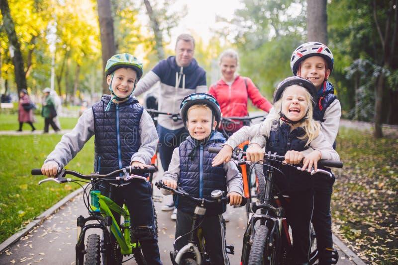 Vacances de sports de famille de thème en parc en nature grande famille caucasienne amicale de six vélos de montagne de personnes image libre de droits