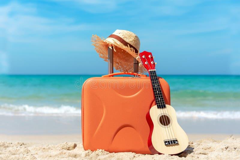 Vacances de vacances voyageant et prévoyant avec la vieux guitare et chapeau de valise sur la plage de sable Voyage pendant les v image stock