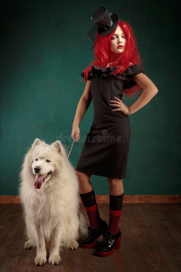 Vacances et Noël de chien d'hiver Fille dans une robe noire et avec les cheveux rouges avec un animal familier dans le studio Fem photos libres de droits