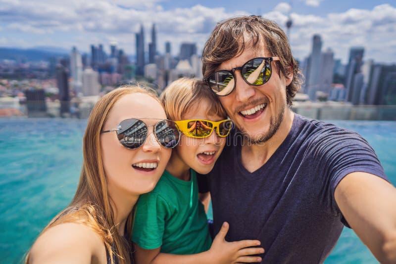 Vacances et technologie Famille heureuse avec l'enfant prenant le selfie ensemble pr?s de la piscine avec des vues panoramiques d photographie stock