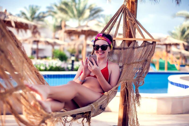 Vacances et technologie Jeune jolie femme dans le maillot de bain utilisant le smartphone s'étendant dans l'hamac près de la pisc photos stock