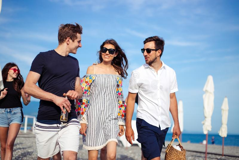 vacances, vacances groupe d'amis ayant l'amusement sur la plage, marcher, la bière de boissons, sourire et étreindre images libres de droits