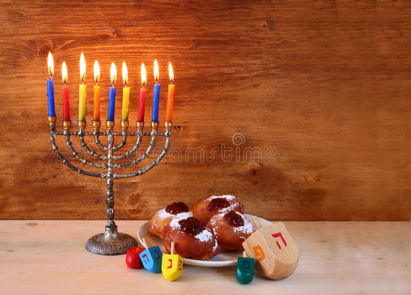 Vacances juives Hanoucca avec le menorah, beignets au-dessus de table en bois rétro image filtrée photo stock