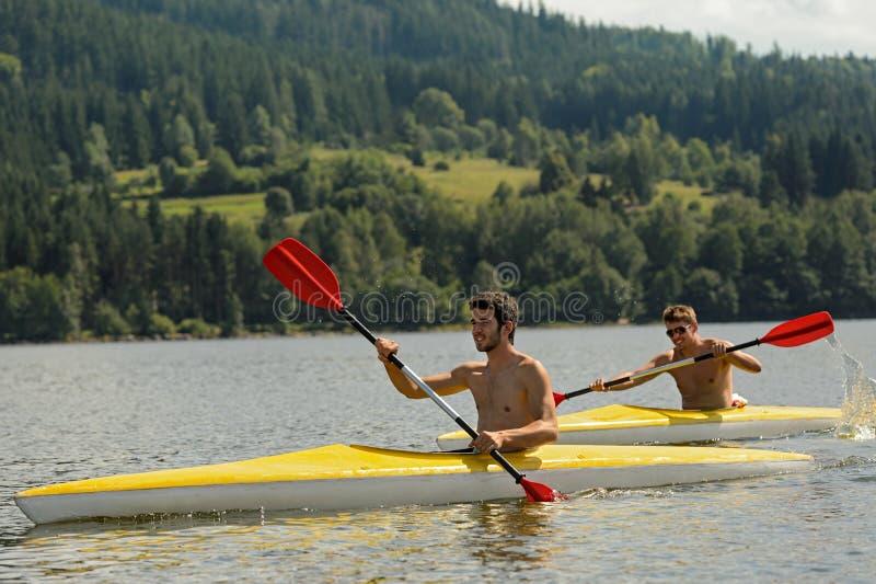 Hommes sportifs Kayaking sur le soleil de rivière images stock