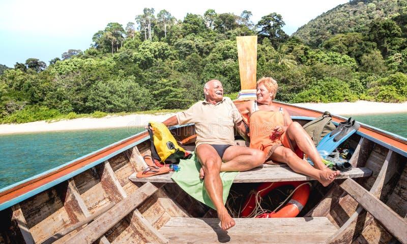 Vacances supérieures de couples détendant à la visite de voyage d'île en île après exploration de plage pendant le voyage de bate photographie stock
