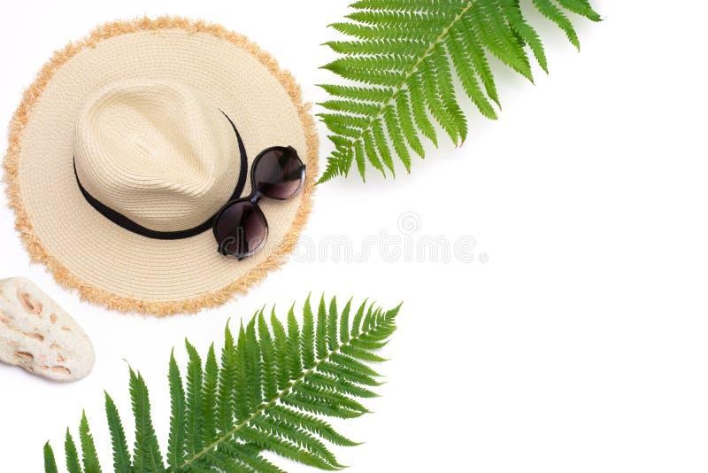 Vacances tropicales Chapeau de soleil de plage de paille, verres de soleil, feuille de fougère sur le blanc Vue supérieure avec l images stock