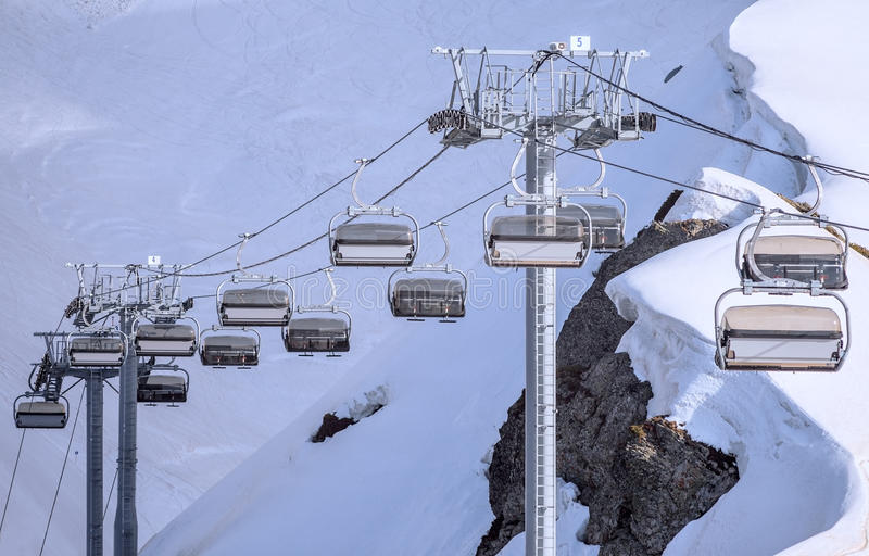 Vacant cableway lift chairs of an empty ski resort at sunny winter day against snowy mountain slopes background royalty free stock photography