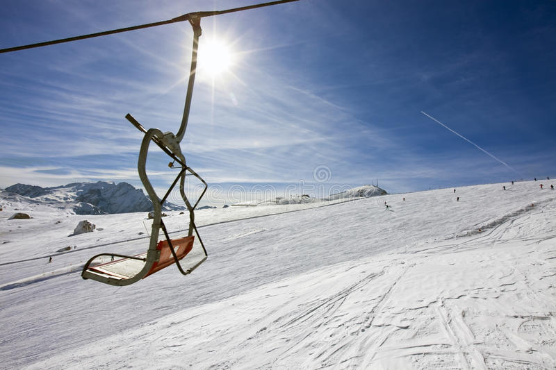 Vacant chair of a ski-lift. Above a ski slope stock photo