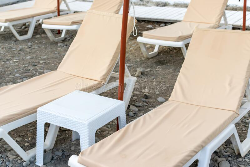 Vacant empty sun loungers with beige pastel matresses and a table on a seashore, coastline, seaside.  stock photos