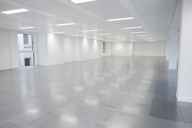 Vacant open plan office space with lights on royalty free stock photography