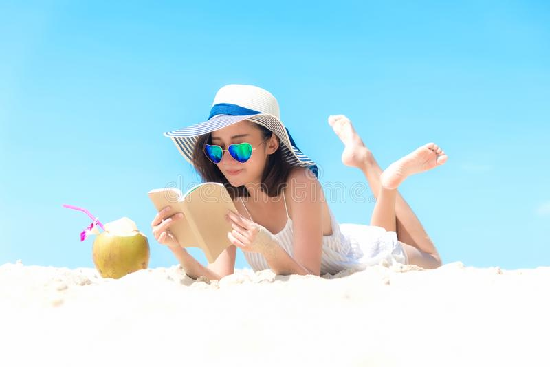 Vacanza di estate Donne asiatiche odoranti che si rilassano, libro di lettura e cocktail bevente della noce di cocco sulla spiagg fotografia stock libera da diritti