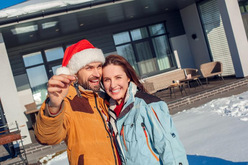 Vacanza di inverno Condizione giovane delle coppie insieme all'aperto con le chiavi dal sorridere della nuova casa allegro immagine stock libera da diritti