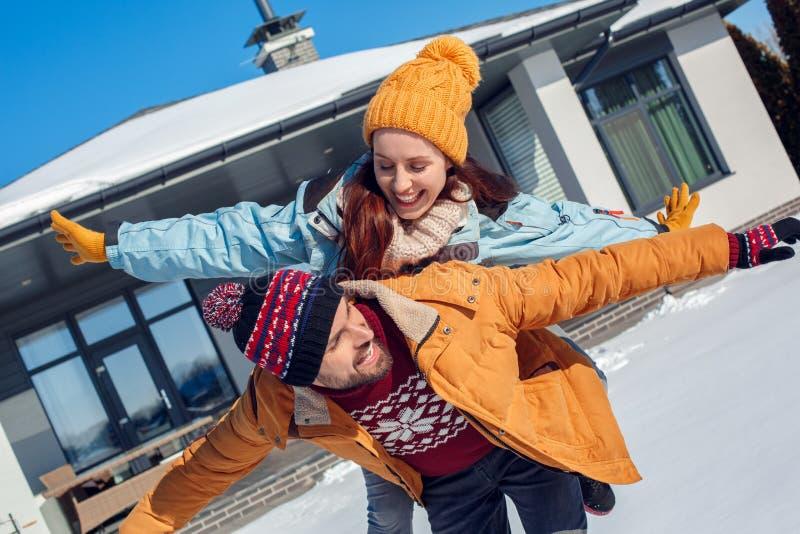 Vacanza di inverno Giovane condizione delle coppie insieme all'aperto vicino alla casa che rende risata volante di posa allegra fotografia stock