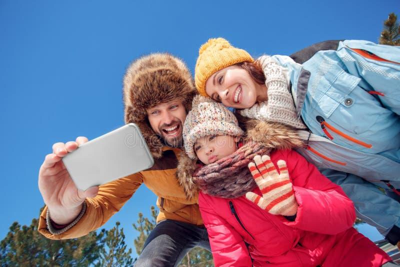 Vacanza di inverno Tempo della famiglia all'aperto che prende insieme selfie sulla vista dal basso allegra sorridente dello smart fotografia stock libera da diritti