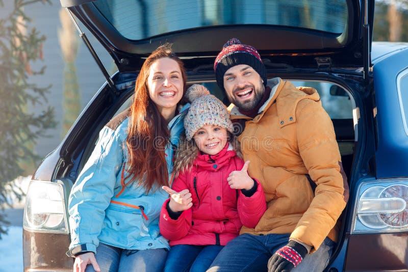Vacanza di inverno Tempo della famiglia all'aperto che sta insieme seduta al tronco di automobile che ride gitl allegro che mostr immagini stock libere da diritti