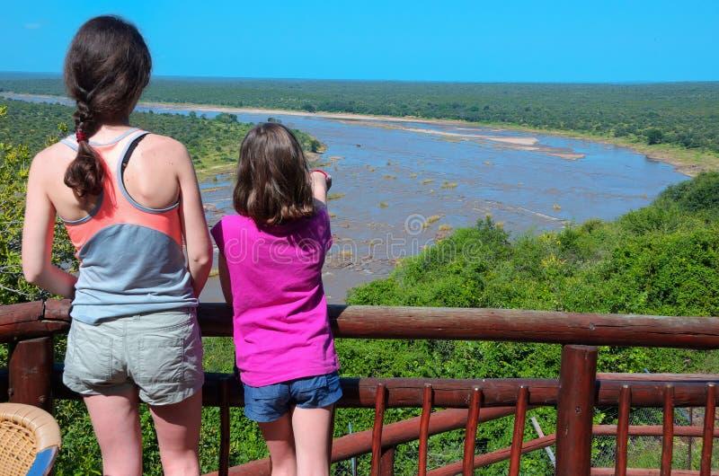 Vacanza di safari della famiglia nel Sudafrica, madre e figlia esaminanti vista del fiume, parco nazionale di Kruger di viaggio t fotografia stock