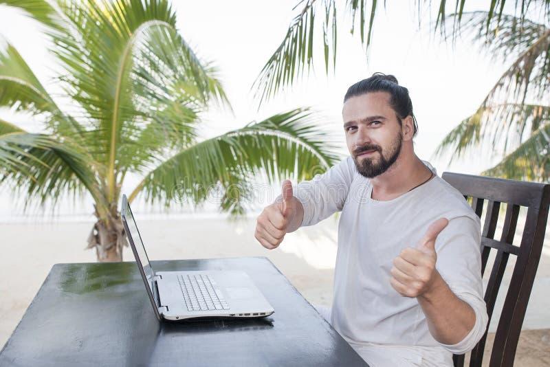 Vacanza e tecnologia Lavoro e viaggio Giovane uomo barbuto facendo uso del computer portatile mentre sedendosi alla barra del caf fotografia stock