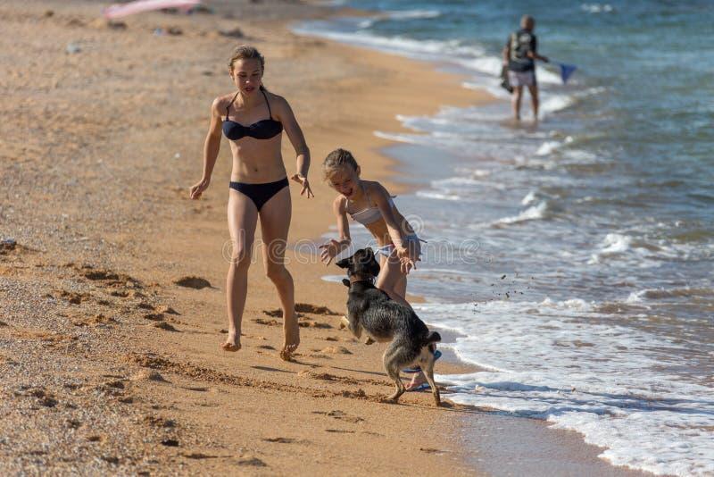Vacanza, giorno di estate sulla spiaggia nel mare, un gioco di tre sorelle immagine stock libera da diritti