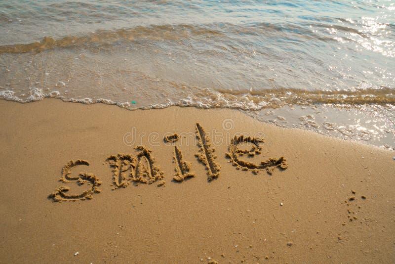 Vacanza sul concetto della spiaggia di sabbia Parole di sorriso scritte nella sabbia sulla spiaggia a Rayong, Tailandia immagine stock libera da diritti