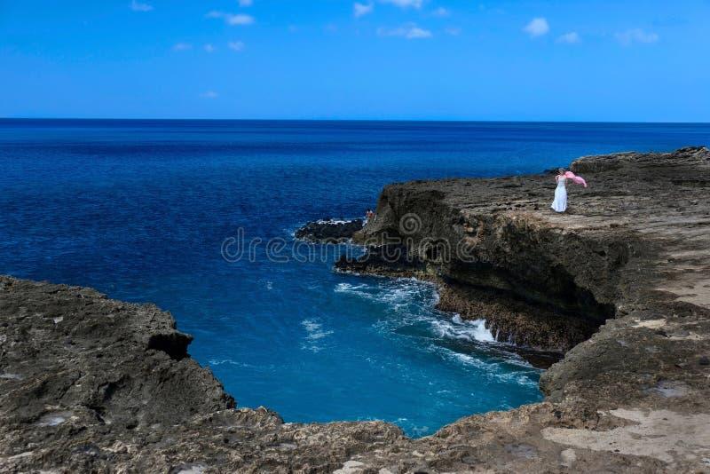 Vacanza sull'Hawai Condizione della donna di medio evo su una scogliera della roccia vulcanica sopra l'oceano con il suo volo del immagine stock
