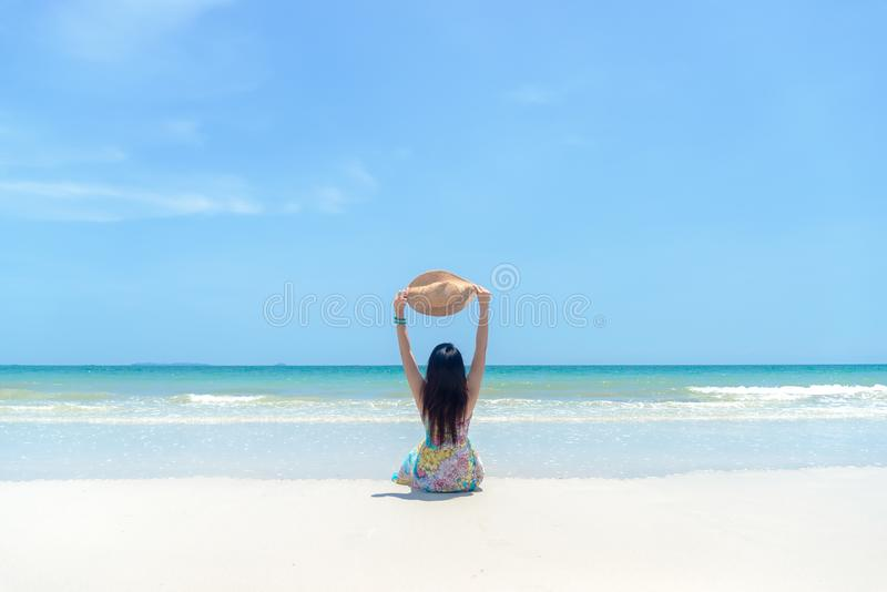 Vacanze di estate Donna asiatica che si siede sulla spiaggia sabbiosa che esamina il mare ed il cielo fotografie stock libere da diritti