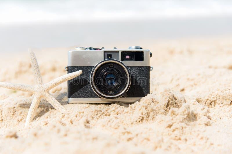 Vacanze di estate Vecchia macchina fotografica d'annata di turismo sulla spiaggia sabbiosa con il pesce della stella fotografia stock libera da diritti