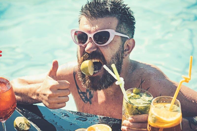 Vacanze estive a Miami Beach o alle Maldive Nuoto dell'uomo ed alcool della bevanda Cocktail con frutta all'uomo barbuto in stagn fotografia stock libera da diritti